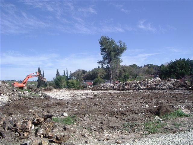דחפור וברקע גגות הבתים